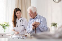 Patient talking to community nurse. Elderly patient talking to young smiling community nurse Royalty Free Stock Photography