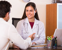 Patient and therapeutist at desk in clinic Stock Photography