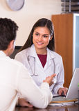 Patient and therapeutist at desk in clinic Royalty Free Stock Photography