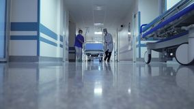 Patient transportation in hospital`s hallway. On surgical bed stock footage