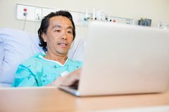 Patient Using Laptop On Hospital Bed Stock Photos