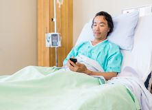Patient Using Mobile Phone On Hospital Bed Stock Photography