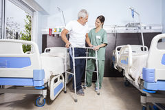 Patient Using Walker While Looking At Nurse At Rehab Center Stock Photos
