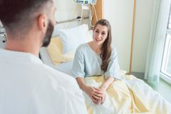 Patient waiting in hospital bed for doctor to see her. During ward round stock images