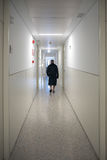 Patient walking alone in a hospital hallway. Patient walking alone in a hospital corridor. Loneliness and illness concept Stock Photo
