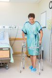 Patient Walking With The Help Of Walker In. Full length of mid adult female patient walking with the help of walker in hospital Royalty Free Stock Photography