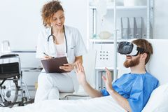 Patient wearing virtual reality glasses. Young trauma patient wearing virtual reality glasses in hospital royalty free stock image