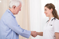 Patient welcome his nurse. Nurse having medical visit in her patient's house stock photography