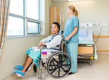 Patient On Wheel Chair With Nurse Standing Behind Royalty Free Stock Photos