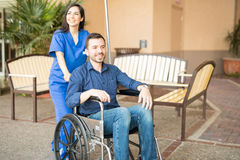 Patient in wheelchair going for stroll. Handsome male patient being pushing on a wheelchair by a nurse, while going for a stroll in the hospital stock photo