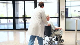 Patient in a wheelchair pushing by a doctor Royalty Free Stock Image