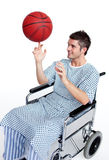 Patient in wheelchair spinning a basket ball. Attractive patient in wheelchair spinning a basket ball on his finger Royalty Free Stock Photography