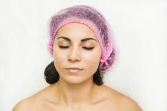A patient woman with closed eyes lies in the doctor`s office. Cosmetic procedures in cosmetology office. Face of the stock photography