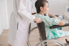 Patient woman is sitting in a wheelchair with doctor standing behind hands support to her royalty free stock photos