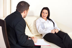 Patient woman talking with psychologist man