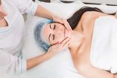Young beautiful girl getting a facial massage in a beauty salon royalty free stock images