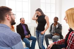 Meeting of support group, therapy session. Patient women standing in circle and telling her problems to therapy group, copy space royalty free stock images