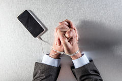 Patient workaholic businessman hands tight to his mobile phone cord Stock Photos