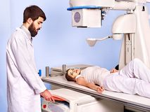 Patient  in x-ray room looking at doctor. Royalty Free Stock Photography