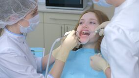 Patient woman on hygienic cleaning of teeth procedure in dentistry by dentist.