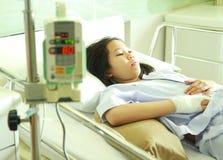 Patiente de femme dans le lit d'hôpital avec IV la machine Photo stock