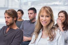 Patienten, die in der Gruppentherapie mit einem Frauenlächeln hören Stockbilder