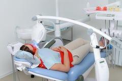 Patienten genomgår ett tillvägagångssätt för tänder som gör vit med en ultraviolett lampa Royaltyfri Fotografi