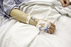 Patienten med dropp fodrar i sjukhussäng Arkivbilder