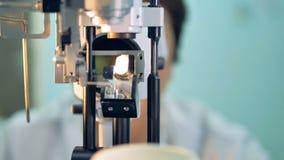 Patienter POV på en ophthalmological slitslampa med en doktor i bakgrunden 4K stock video