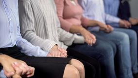 Patients holding hands and sitting in row at group therapy session, support. Stock photo royalty free stock images