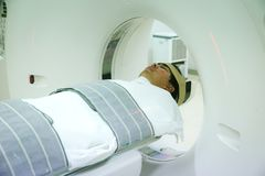Patients screening on CT scanner. Man Undergoing CT Scan While Doctor`s Using Computers. stock photos