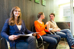 Patients in the waiting room of a doctors office Royalty Free Stock Images