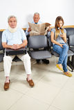 Patients waiting in waiting room. Three patients waiting in a waiting room of a hospital Royalty Free Stock Images