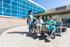 Patients On Wheelchair By Nurses Outside Hospital stock photo
