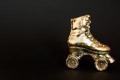 Patim de rolo dourado contra o fundo preto Foto de Stock