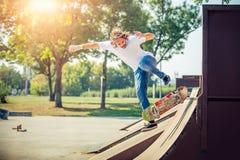 Patin d'équitation de jeune homme au parc et à la chute vers le bas photographie stock