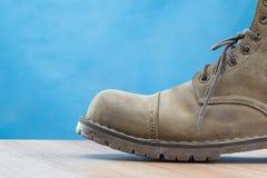Patina-Lederstiefel auf Holzoberfläche und blauem Hintergrund Lizenzfreie Stockfotos