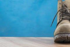 Patina-Lederstiefel auf Holzoberfläche und blauem Hintergrund Lizenzfreies Stockfoto