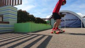 Patinador activo joven que hace truco del tirón y que da vuelta a longboard almacen de metraje de vídeo