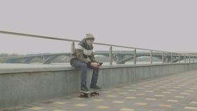 Patinador adolescente que escucha la música en el teléfono al aire libre metrajes