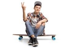 Patinador adolescente que se sienta en un longboard y que hace un gesto de la paz Fotografía de archivo