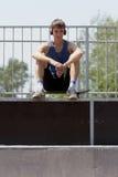 Patinador cansado que se sienta en una rampa en auriculares Imagenes de archivo