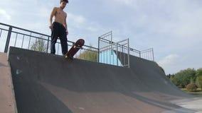 Patinador con un descenso desnudo del torso en rampa en el skatepark de madera, a cámara lenta almacen de video