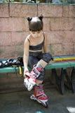 Patinador de la muchacha en el banco en el parque Fotos de archivo libres de regalías