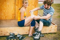 Patinador de la mujer con la rodilla herida de la pierna Foto de archivo