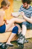 Patinador de la mujer con la rodilla herida de la pierna Imágenes de archivo libres de regalías