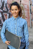 Patinador de sexo femenino atractivo que lleva a cabo a su tablero en la sonrisa del pasillo del patín Fotos de archivo