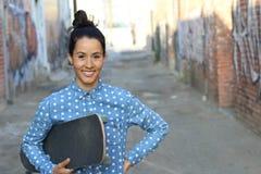 Patinador de sexo femenino atractivo que lleva a cabo a su tablero en la sonrisa del pasillo del patín Imagenes de archivo