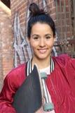 Patinador de sexo femenino atractivo que lleva a cabo a su tablero en la sonrisa del pasillo del patín Imagen de archivo libre de regalías