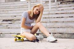 Patinador de sexo femenino joven que tiene dolor de cabeza Imagenes de archivo